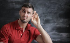 Man in red t-shirt frowning with hand up to ear like he's listening