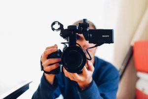 Man holding Sony video camera to camera